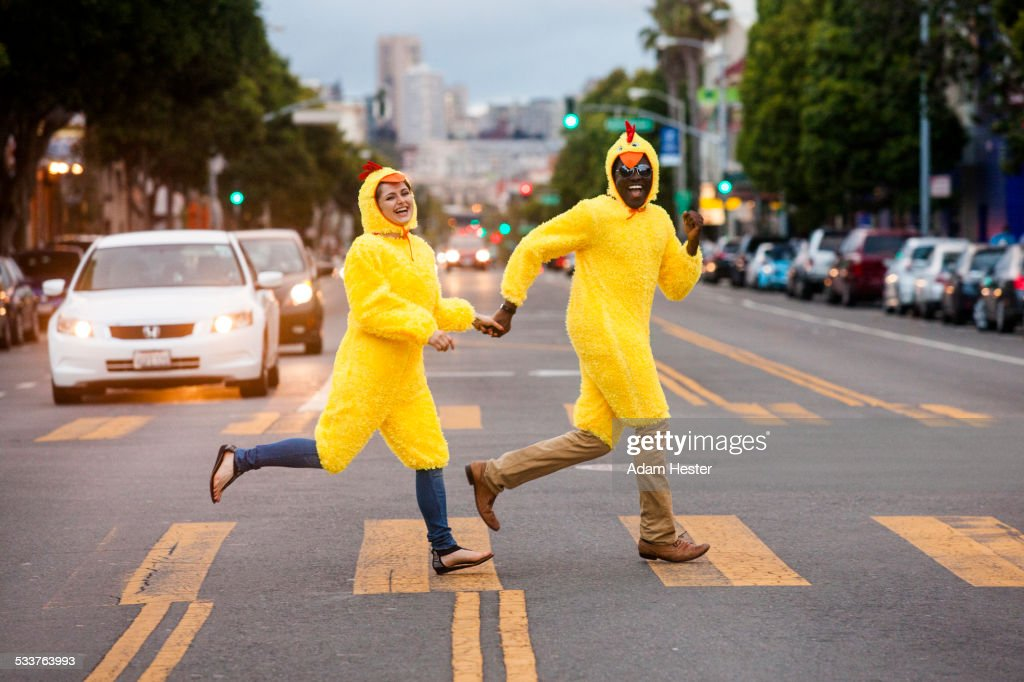 Couple in chicken costumes crossing city street : Stock Photo