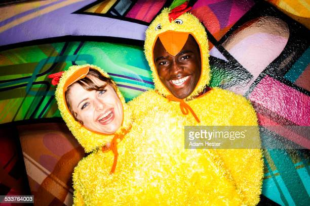 couple in chicken costumes smiling near graffiti wall - funny rooster stock photos and pictures