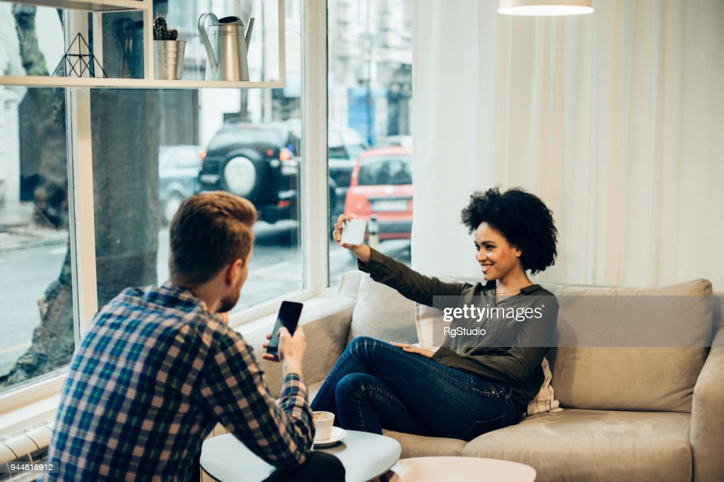 Couple in coffee shop, woman making selfie : Stock Photo