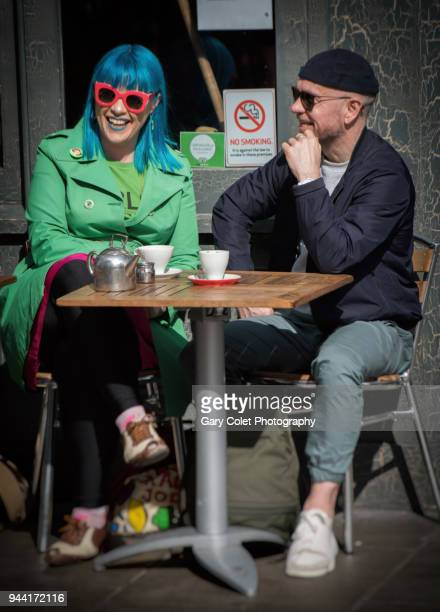couple in colorful clothes talking and laughing outside a cafe - gary colet stock pictures, royalty-free photos & images