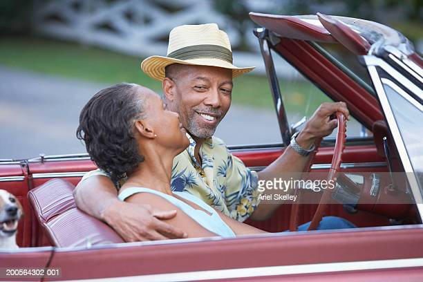 Couple in convertible car, arm around, smiling