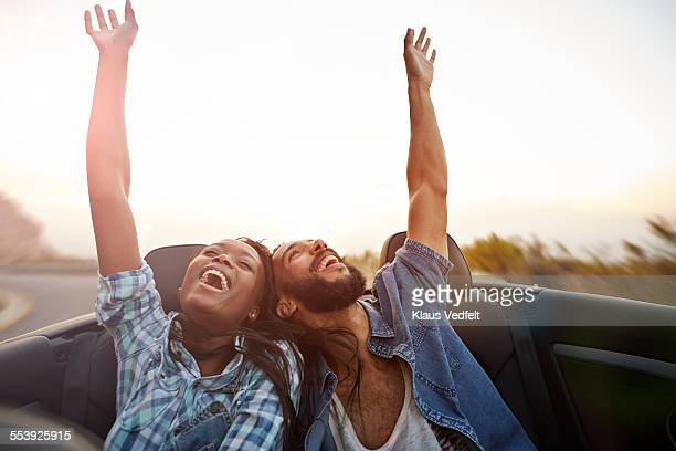 Couple in convertible car laughs with arms raised