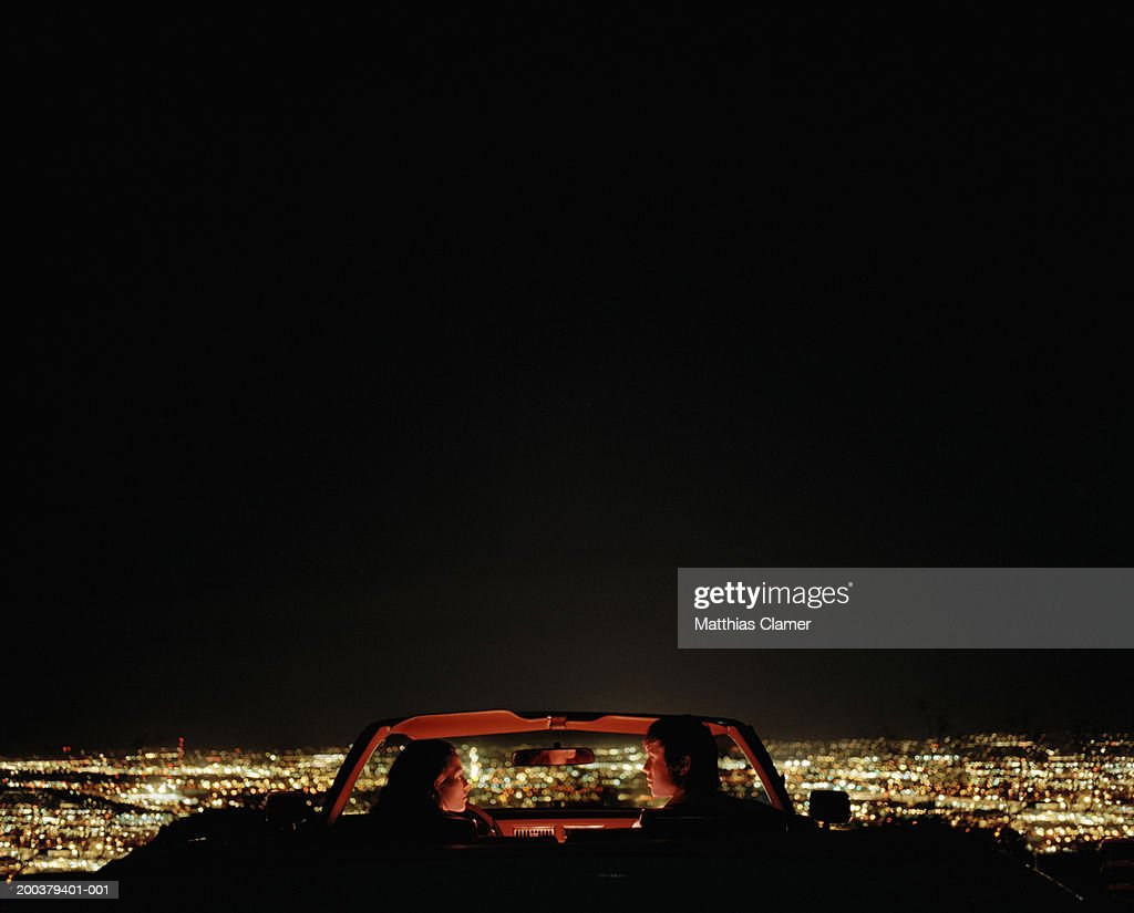 Couple in convertible overlooking city, rear view : Stock Photo