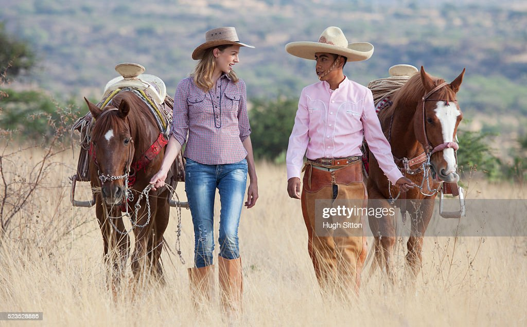 Couple in cowboy hats leading horses : Stock Photo