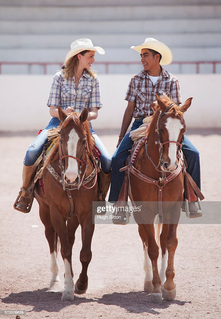 Couple in cowboy hats riding horses : Stock Photo