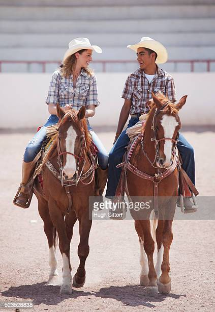 couple in cowboy hats riding horses - hugh sitton stock pictures, royalty-free photos & images