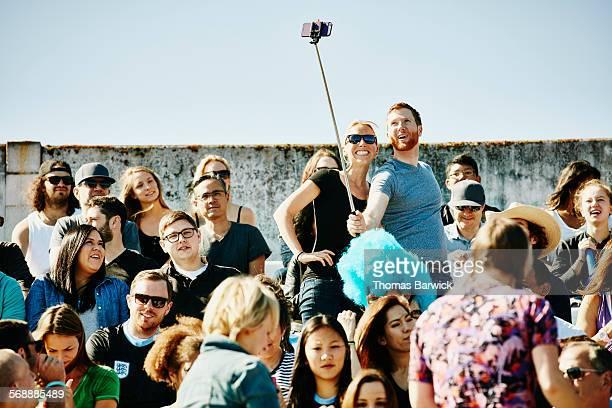 Couple in crowd in stadium using selfie stick