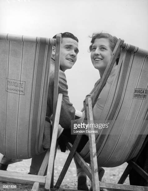 A couple in deckchairs at the popular seaside resort of Margate in Kent