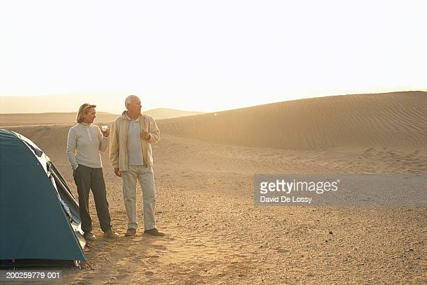 Couple in desert by dome tent