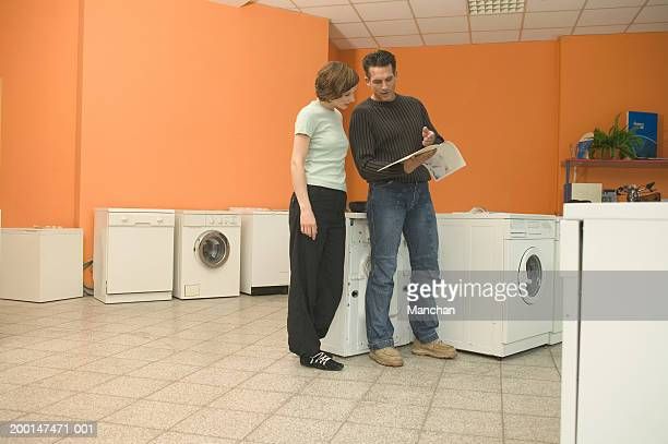Couple in electrical appliance store, looking at brochure