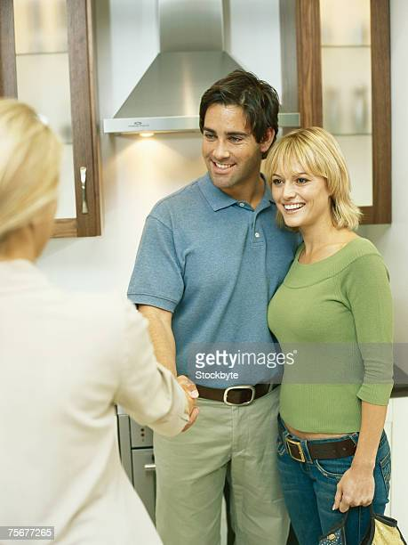 Couple in electrical shop, female salesclerk shaking hands with man
