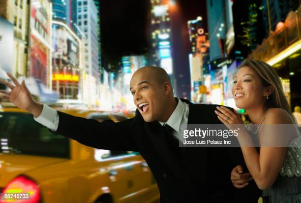 couple in elegant clothing hailing taxi at night - evening gown stock pictures, royalty-free photos & images