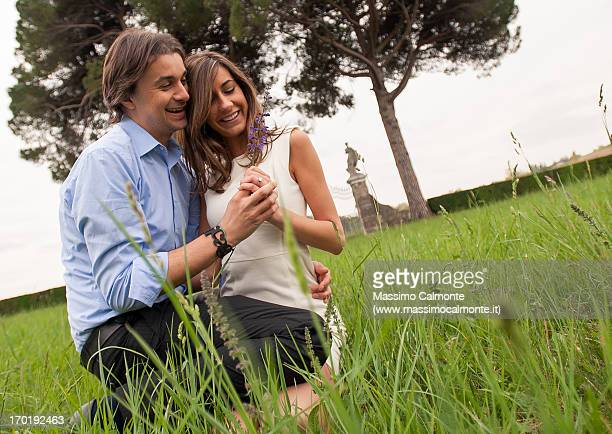 Couple in elegant dresses sitting on a green grass
