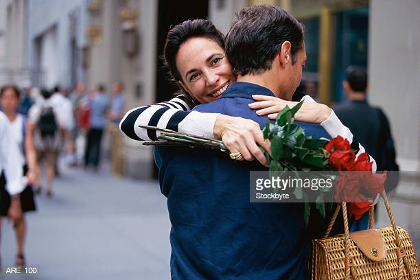 Couple in embrace; woman holding bouquet of roses and smiling