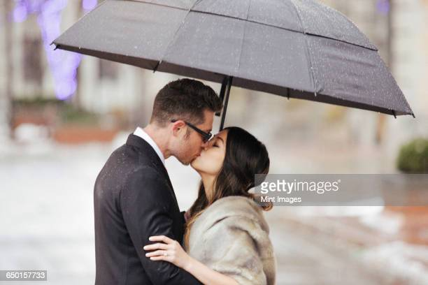 A couple in evening dress, a man and woman kissing under an umbrella.