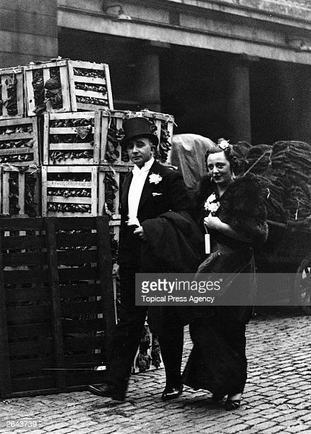 A couple in evening dress pass through Covent Garden fruit and vegetable market on their way to the opening night of 'Othello' at the Opera House