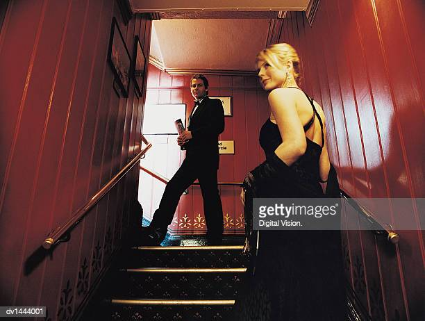 couple in evening wear ascending stairs in a theatre - evening wear stock pictures, royalty-free photos & images
