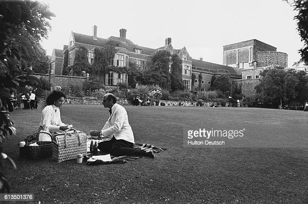 A couple in evening wear enjoying the traditional picnic on the lawns of Glyndebourne whilst attending the annual opera festival