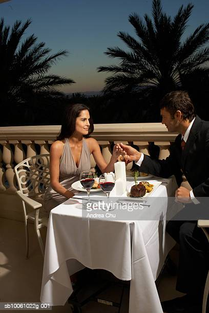 Couple in evening wear having dinner on balcony, holding hands