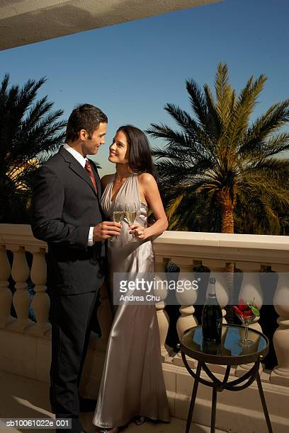Couple in evening wear standing on balcony, drinking champagne