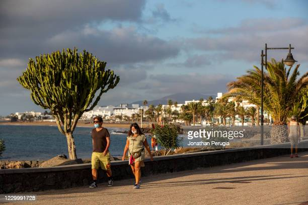 Couple in face masks walk along the promenade in Playa Matagorda, Lanzarote, Spain on 22nd November 2020. Beaches and resorts across the island are...