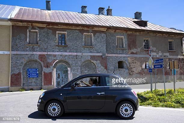 Couple in Fiat 500 passe signpost on The Stelvio Pass Passo dello Stelvio Stilfser Joch in Italy head for Switzerland