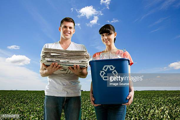 Couple in field holding recycling bin and pile of newspapers