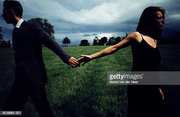 couple in field, letting go of each other's hands - heterosexuelles paar stock-fotos und bilder