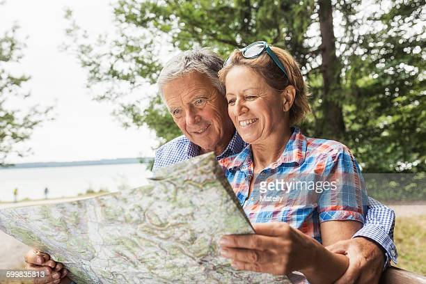 couple in forest, looking at map, smiling - heterosexual couple stock pictures, royalty-free photos & images