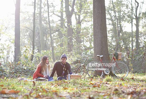Couple in forest with vintage bikes and picnic.