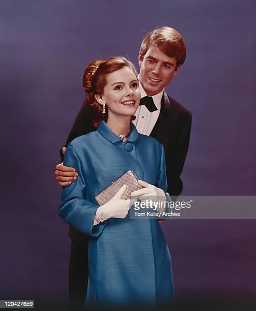 Couple en tenues habillées debout contre fond bleu, smil