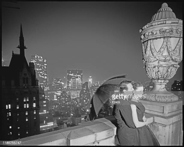 A couple in formal evening wear hold an umbrella on a rooftop for a night time fashion shoot in Manhattan New York