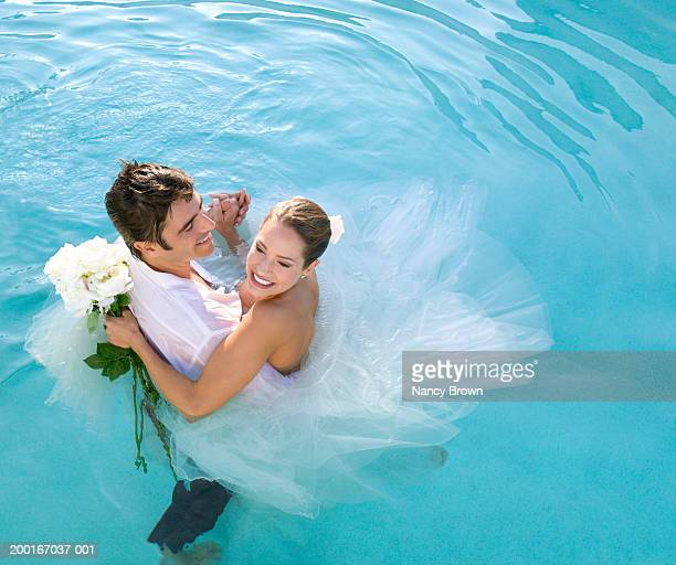 Couple in formal wear dancing in pool, elevated view