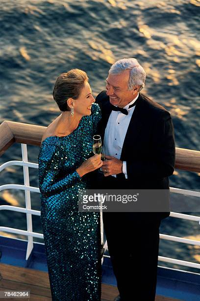 couple in formal wear drinking champagne on cruise - カクテルドレス ストックフォトと画像