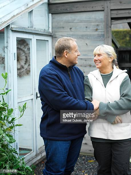 A couple in front of a greenhouse.