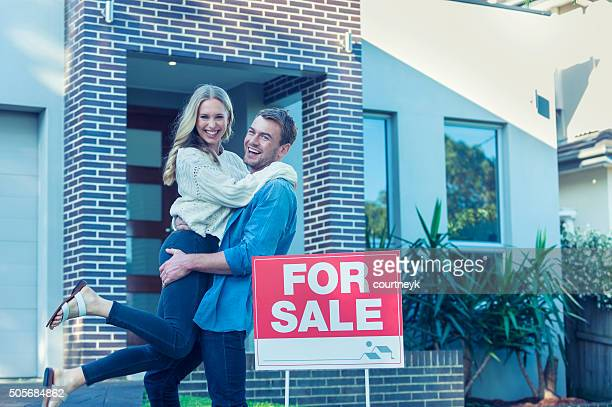 Couple in front of a new home.