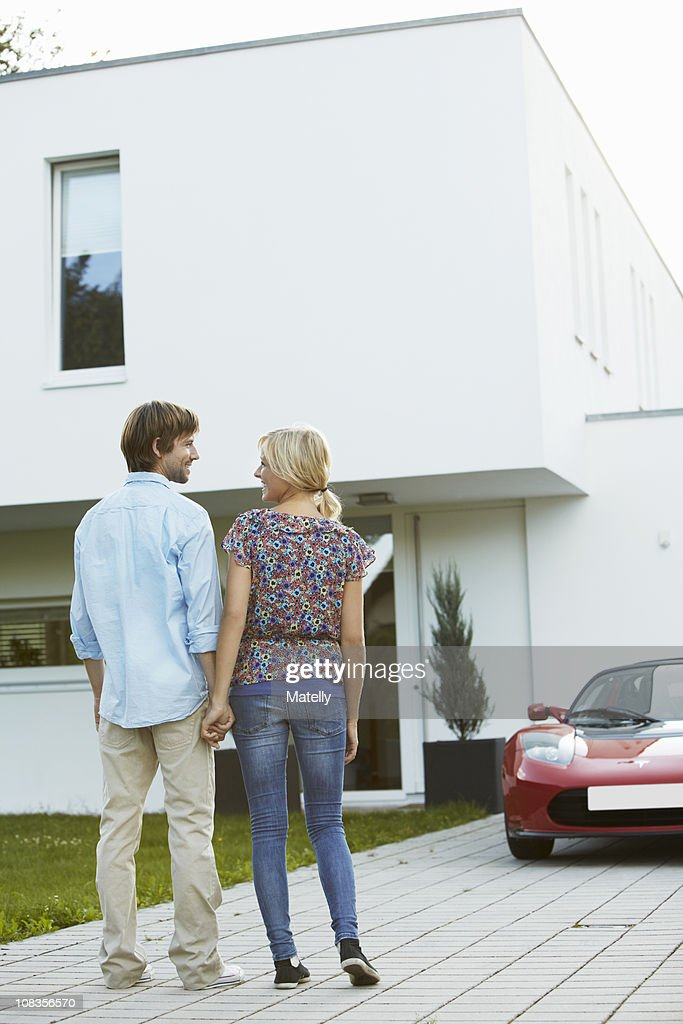 Couple in front of house + electric car : Stock Photo