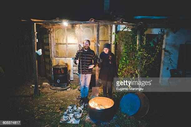 Couple in front of shed holding tongs, with pottery by fire in barrel