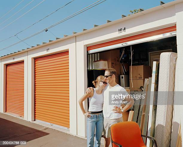 couple in front of storage shed, man's arm around woman - storage compartment stock pictures, royalty-free photos & images