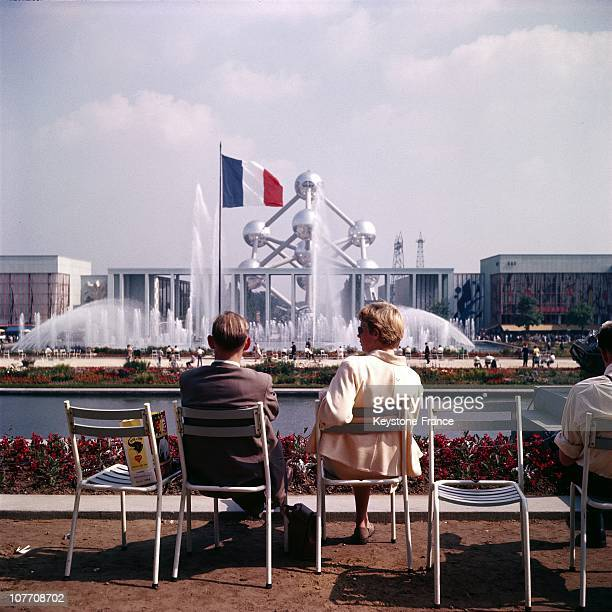 Couple In Front Of The French Flag And Atomium During The Exposition Universelle De Bruxelles On January 01St 1958