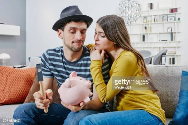 Couple in furniture store demolishing piggy bank