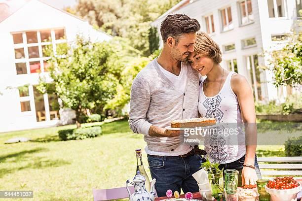 Couple in garden having tender moment, man holding cake