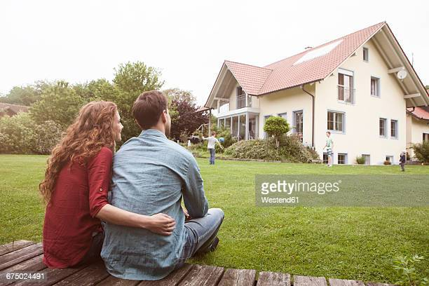 couple in garden looking at house - wohnhaus stock-fotos und bilder