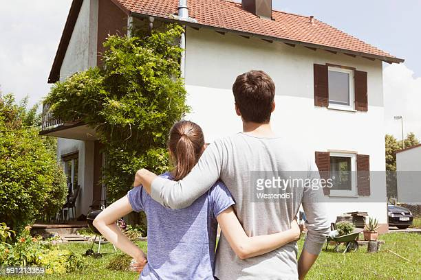 Couple in garden looking at residential house