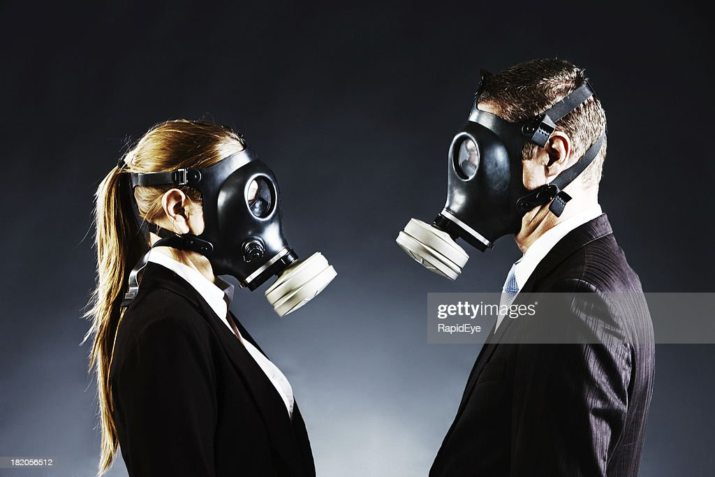 Couple in gas masks face off confronting each other : Stock Photo