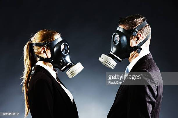 couple in gas masks face off confronting each other - gas mask stock pictures, royalty-free photos & images