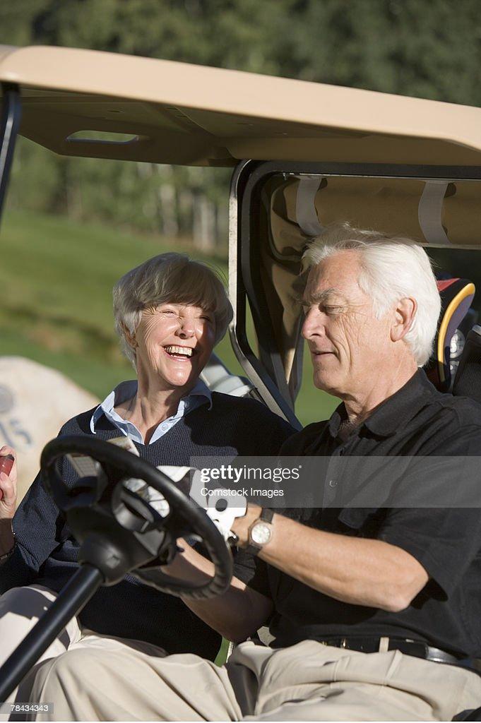 Couple in golf cart : Stockfoto