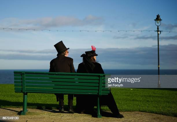 Couple in Gothic Victoriana clothing sit and look out over the North Sea during the Whitby Goth Weekend on October 27, 2017 in Whitby, England. The...