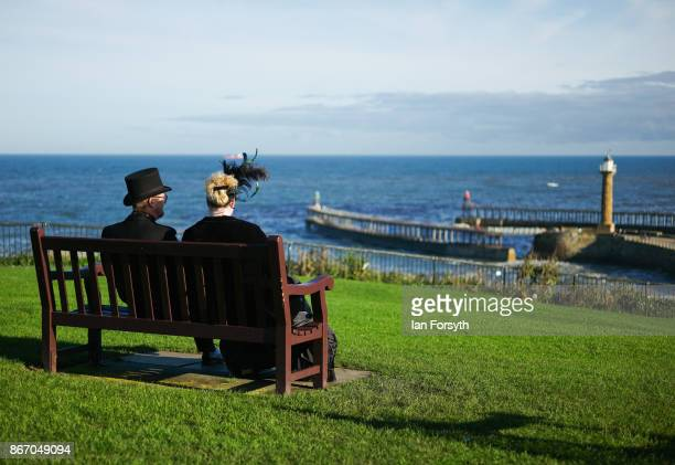 Couple in Gothic Victoriana clothing sit and look out over the harbour during the Whitby Goth Weekend on October 27, 2017 in Whitby, England. The...