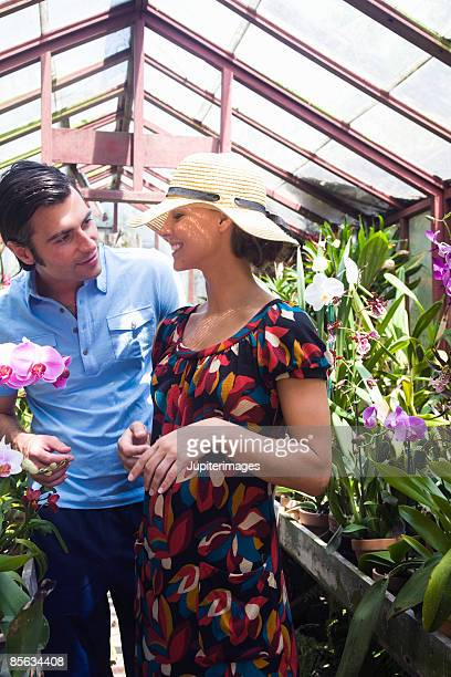 Couple in greenhouse with orchids